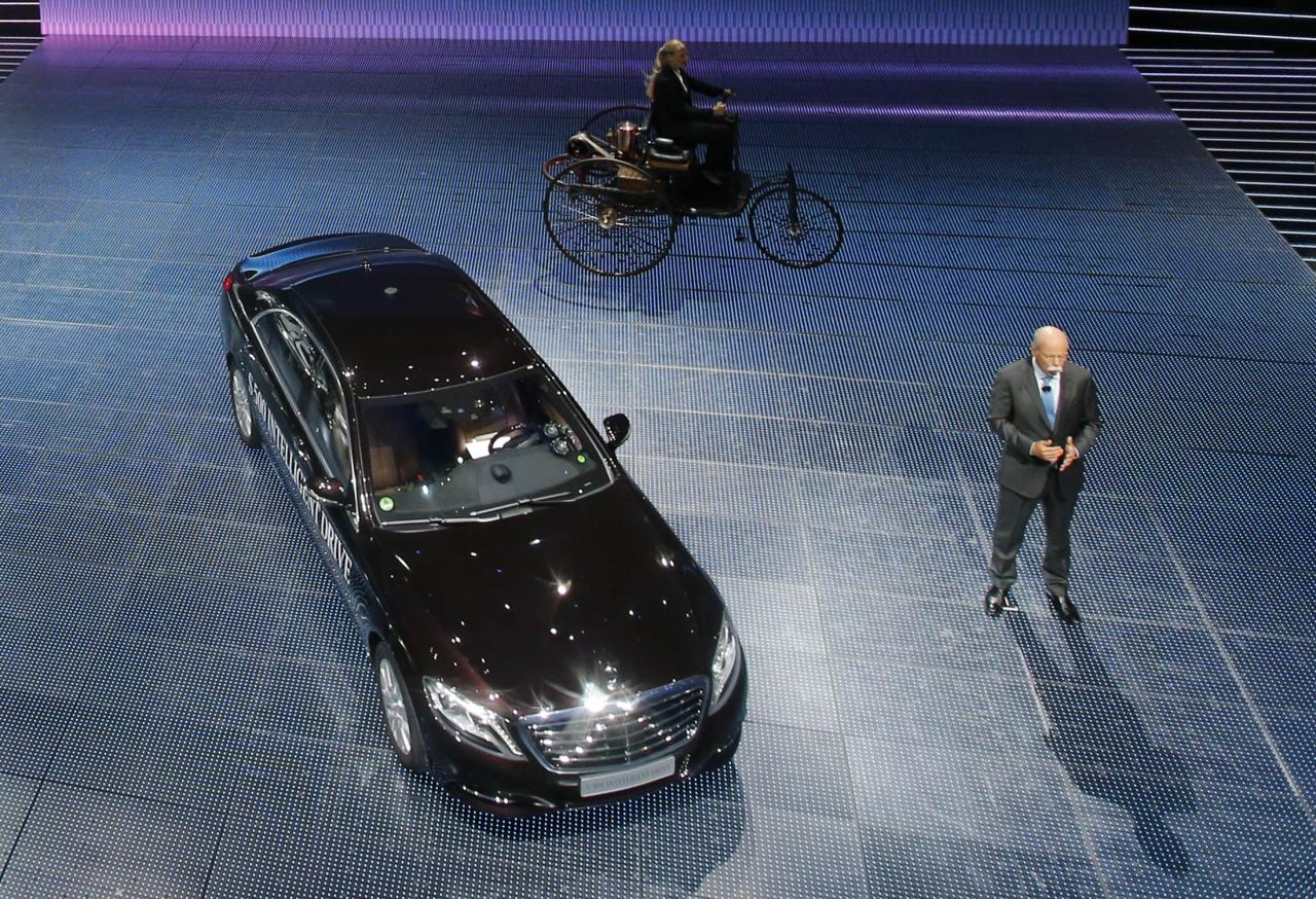 Daimler Chief Executive Dieter Zetsche presents the Mercedes S500 Intelligent Drive car, the first self-steered Mercedes, during its world premiere on media night at the Frankfurt motor show September 9, 2013. The world's biggest auto show is open to the public September 14 -22. At rear, a woman drives a replica of the Benz Patent-Motorwagen, widely regarded as the world's first motor-driven vehicle from 1866. REUTERS/Wolfgang Rattay (GERMANY - Tags: BUSINESS TRANSPORT)