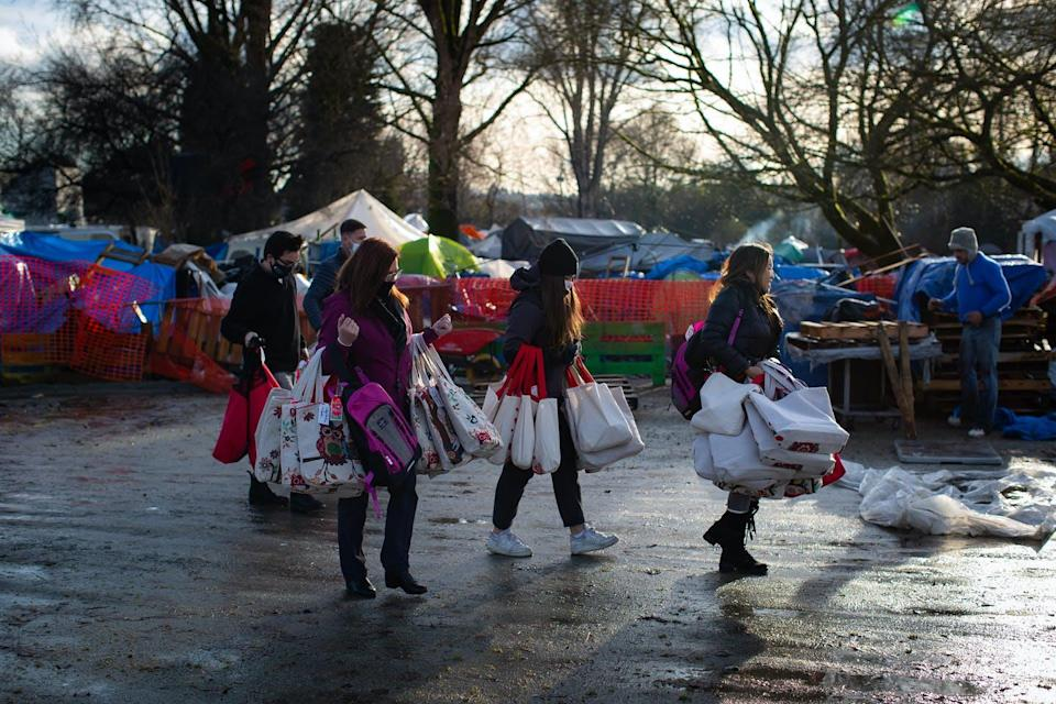 People carry bags of donations to a homeless encampment.