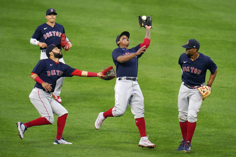 Boston Red Sox third baseman Rafael Devers, center, makes a catch on a fly ball hit by Baltimore Orioles' Cedric Mullins, not visible, as Red Sox's Marwin Gonzalez, font left, Enrique Hernandez, back left, and Xander Bogaerts look on during the first inning of a baseball game, Saturday, April 10, 2021, in Baltimore. (AP Photo/Julio Cortez)