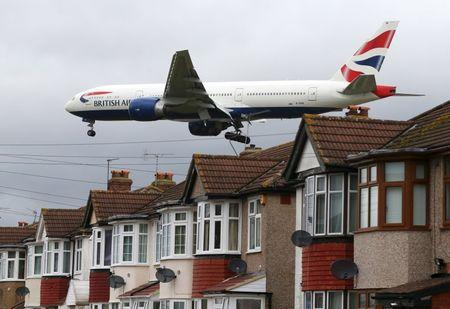 An aircraft  passes over houses at it lands at Heathrow Airport near London, Britain