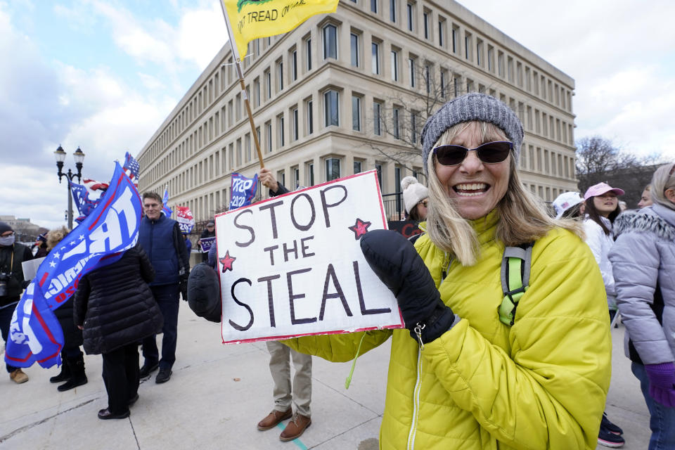 Alyss Kovach holds a sign outside the Richard H. Austin state office building during a rally in Lansing, Mich., Saturday, Nov. 14, 2020. Michigan's elections board is meeting to certify the state's presidential election results. (AP Photo/Paul Sancya)