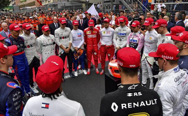 The drivers clap hands around a red helmet on a podest, reading 'Thank you Niki', during a minute of silence to tribute F1 legend Niki Lauda prior the Monaco Formula One Grand Prix race, at the Monaco racetrack, in Monaco, Sunday, May 26, 2019. The former F1 champion Niki Lauda died last week. (Andrej Isakovic/Pool Photo via AP)