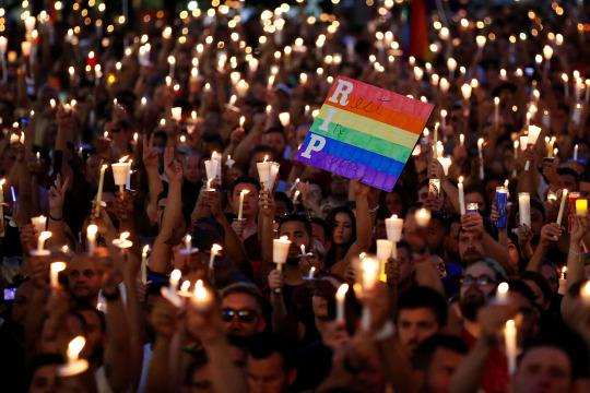 People take part in a candlelight memorial service on Monday night, the day after a mass shooting at the gay nightclub Pulse in Orlando. (Photo: Carlo Allegri/Reuters)