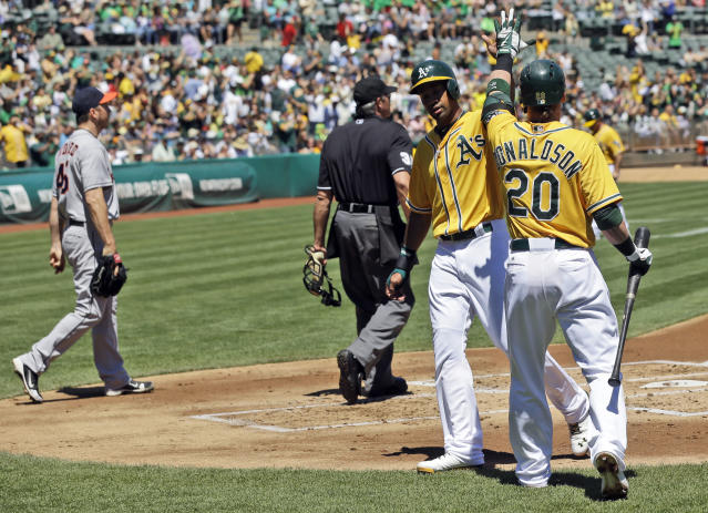 Oakland Athletics' Chris Young, center, is greeted at the plate by Josh Donaldson (20) after Young scored on a double by Jed Lowrie during the first inning of a baseball game on Thursday, Aug. 15, 2013, in Oakland, Calif. (AP Photo/Marcio Jose Sanchez)
