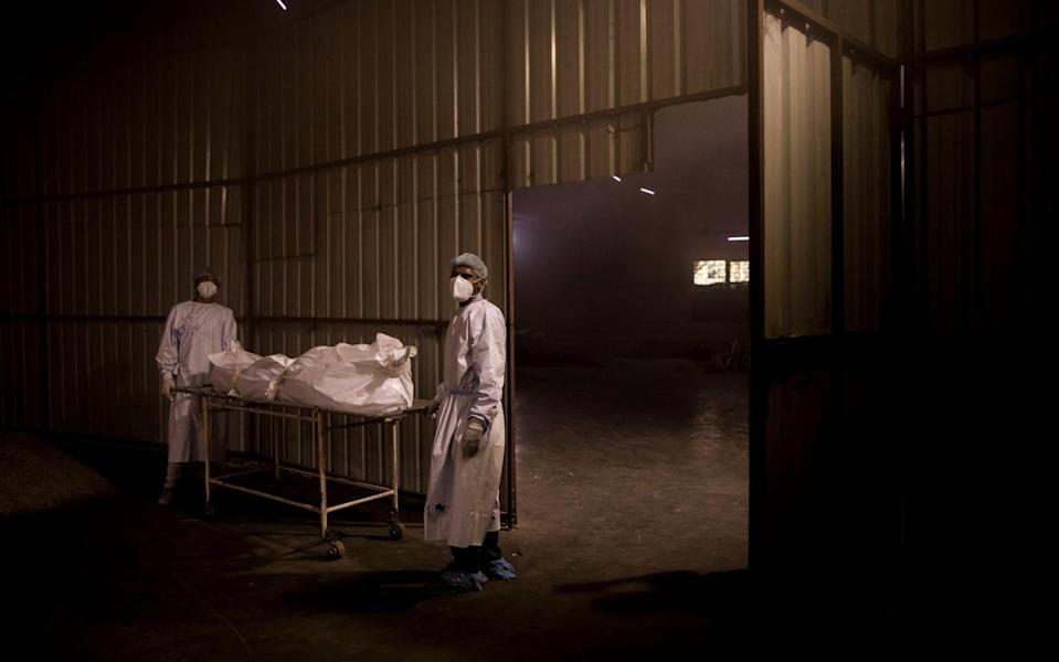Workers transfer the body of a patient who died of coronavirus for his last rites at a crematorium in New Delhi, India - Anindito Mukherjee/Getty Images