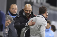 Manchester City's head coach Pep Guardiola, centre, pats Fulham's manager Scott Parker on the back at the end of an English Premier League soccer match between Fulham and Manchester City at the Craven Cottage stadium in London, England, Saturday March 13, 2021. (Catherine Ivill/Pool via AP)