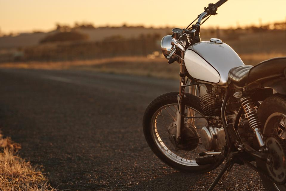 Vintage motorcycle parked on empty country road. Vintage motorbike standing at the side of the road in evening.