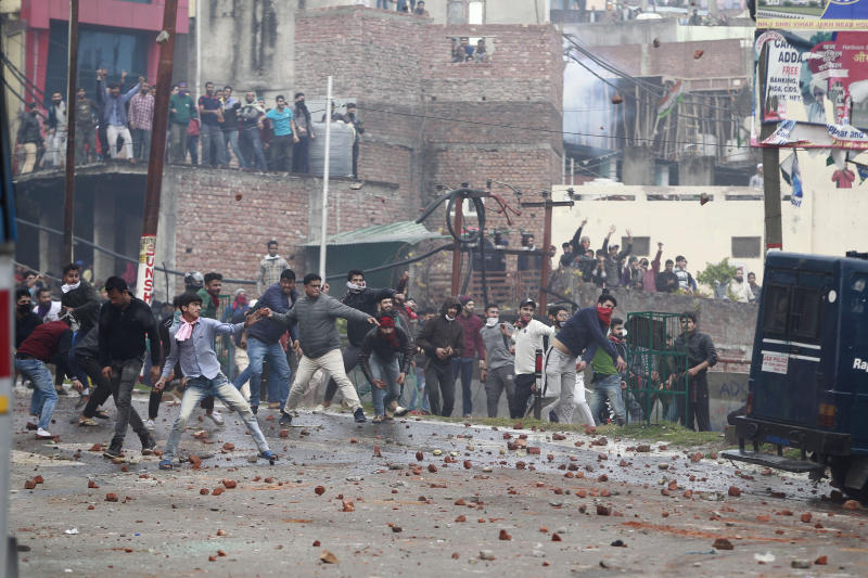 Protestors throw stones during a clash between communities while protesting against Thursday's attack on a paramilitary convoy that killed at least 40 in Kashmir, in Jammu, India, Friday, Feb. 15, 2019. Prime Minister Narendra Modi placed the blame for Thursday's bombing squarely on neighboring Pakistan, which India accuses of supporting rebels in Kashmir. The attack has raised tensions elsewhere in Hindu-majority India. Hundreds of residents carrying India's national flag in Hindu-dominated Jammu city in the Muslim-majority state burned vehicles and hurled rocks at homes in Muslim neighborhoods, officials said. (AP Photo/Channi Anand)