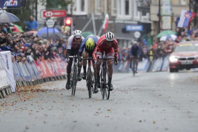 Denmark's Mads Pedersen sprints ahead of Italy's Matteo Trentin and Switzerland's Stefan Kung to win the men elite race, at the road cycling World Championships in Harrogate, England, Sunday, Sept. 29, 2019. (AP Photo/Manu Fernandez)