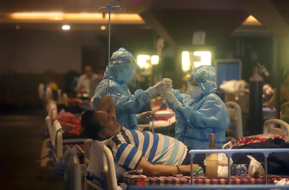 <p>Health workers attend to Covid-19 patients at a makeshift Delhi hospital </p> (Reuters)