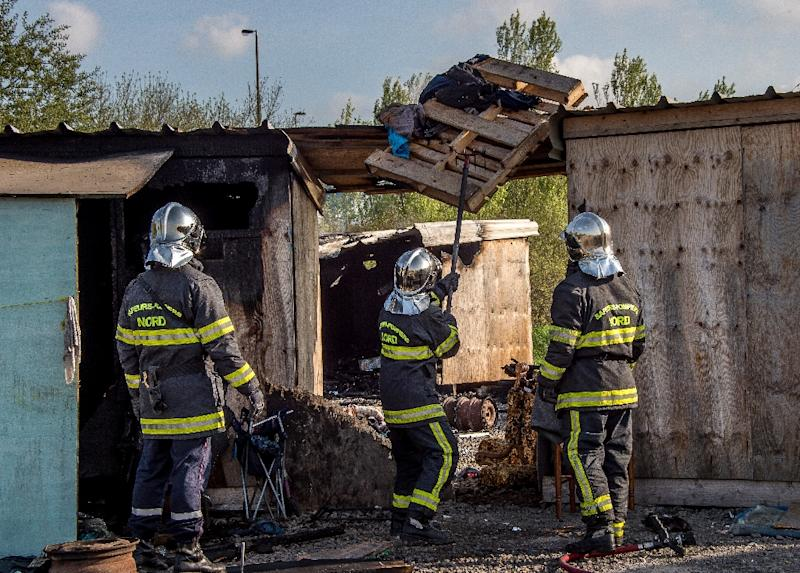 French firemen inspect a burnt hut at the Grande-Synthe migrant camp on the outskirts of Dunkirk, on April 11, 2017