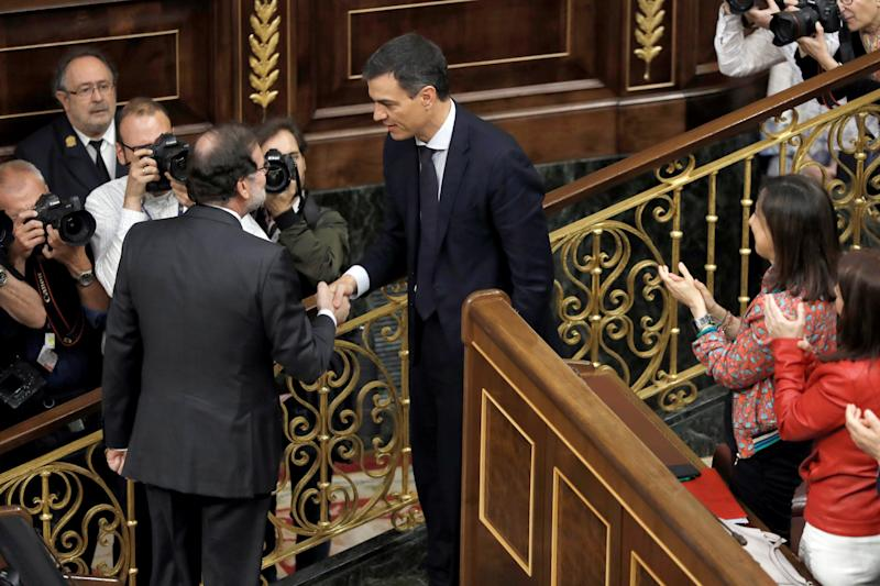 TOPSHOT - Spanish out-going Prime Minister Mariano Rajoy (L) shakes hands with Spain's new Prime Minister Pedro Sanchez after a vote on a no-confidence motion at the Lower House of the Spanish Parliament in Madrid on June 01, 2018. - Spain's parliament ousted on June 1, 2018 Prime Minister Mariano Rajoy in a no-confidence vote sparked by fury over his party's corruption woes, with his Socialist arch-rival Pedro Sanchez automatically taking over. (Photo by Emilio Naranjo / POOL / AFP) (Photo credit should read EMILIO NARANJO/AFP/Getty Images)