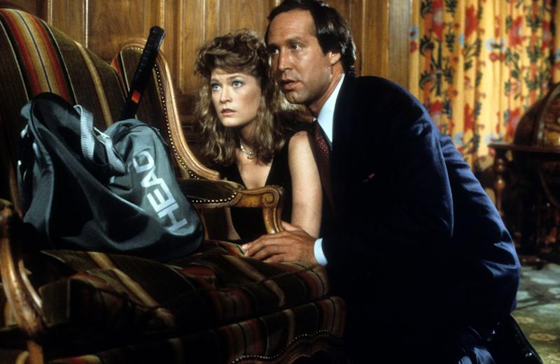 Dana Wheeler Nicholson and Chevy Chase hide behind a couch in a scene from the film 'Fletch', 1985. (Photo by Universal/Getty Images)