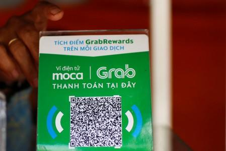 A mobile e-payment logo from Grab is seen at a street food stall in Ho Chi Minh city in Vietnam