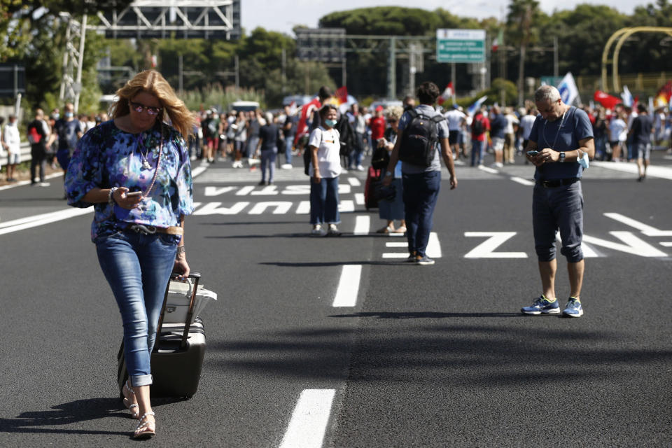 Passengers push their trolleys as Alitalia workers blocked the road leading to the Rome Leonardo Da Vinci international airport following a protest in Fiumicino, Friday, Sept. 24, 2021. Alitalia, which has been in the red for more than a decade, is due to formally exit the airline market next month and be replaced by a new national carrier ITA, or Italy Air Transport. The European Commission has given the go-ahead to a 1.35 billion euro ($1.58 billion) injection of government funding into the new airline, but ITA is only planning to hire around a quarter of the estimated 10,000 Alitalia employees. (Cecilia Fabiano/LaPresse via AP)