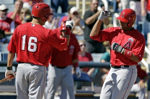 Los Angeles Angels' Hank Conger (16) congratulates teammate Vernon Wells after Wells' home run during the second inning of an exhibition spring training baseball game against the Milwaukee Brewers, Saturday, March 2, 2013, in Phoenix. (AP Photo/Morry Gash)