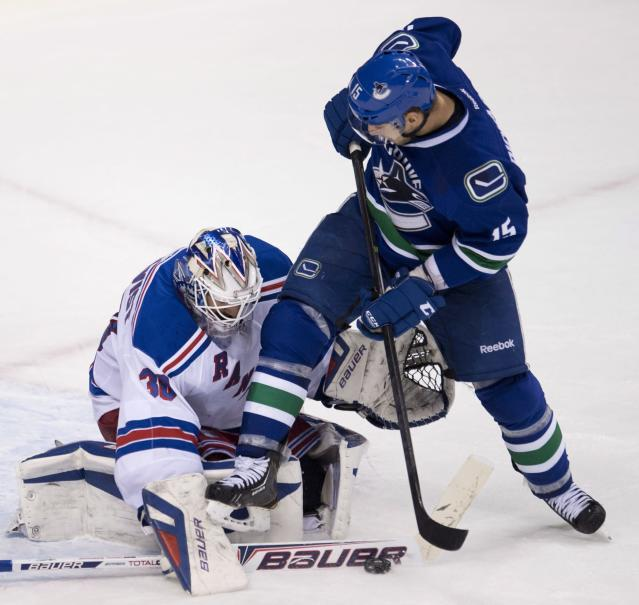 Vancouver Canucks center Brad Richardson (15) tries to get a shot past New York Rangers goalie Henrik Lundqvist (30) during the third period of an NHL hockey game Tuesday, April 1, 2014, in Vancouver, British Columbia. (AP Photo/The Canadian Press, Jonathan Hayward)