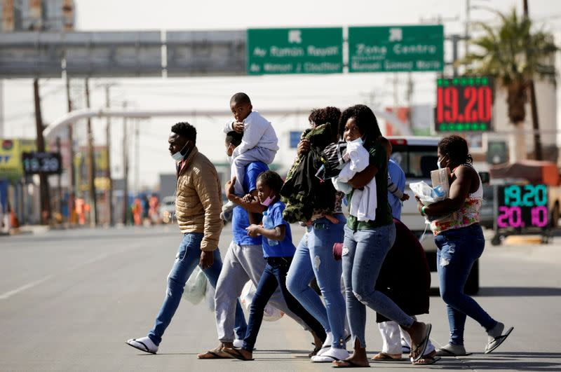 Migrants from Haiti walk near the Zaragoza-Ysleta international border bridge after being deported from the United States, in Ciudad Juarez