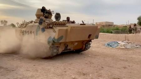 Still image from video shows Syrian rebel fighters driving a tank through a field near Tal Abyad