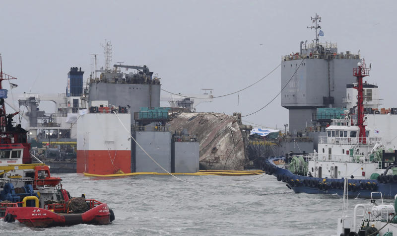 The sunken Sewol ferry is loaded onto a semi-submersible transport vessel during the salvage operation in waters off Jindo, South Korea, Saturday, March 25, 2017. Salvage crews towed the corroded 6,800-ton South Korean ferry toward a transport vessel on Friday after it was successfully raised from waters off the country's southwest coast. The massive attempt to bring the ferry back to shore, nearly three years after it sank, killing 304 people, is being closely watched by a nation that still vividly remembers the horrific accident. (Lee Jin-wook/Yonhap via AP)