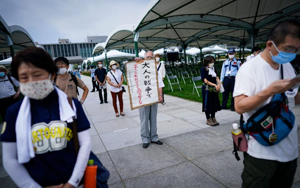 An elderly man holds up a sign that reads 'Don't let children cry because of adults' war' as he queues in line to pray at Peace Memorial Park in Hiroshima - DAI KUROKAWA/EPA-EFE/Shutterstock/Shutterstock