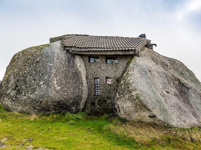 A house is visible between two large rocks.