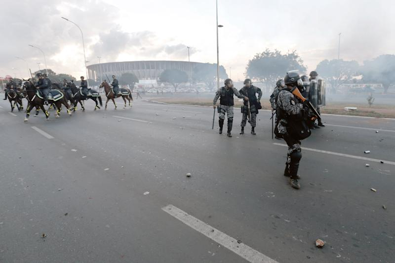 Military policemen launch tear gas grenades against indigenous demonstrators during a protest against the FIFA World Cup