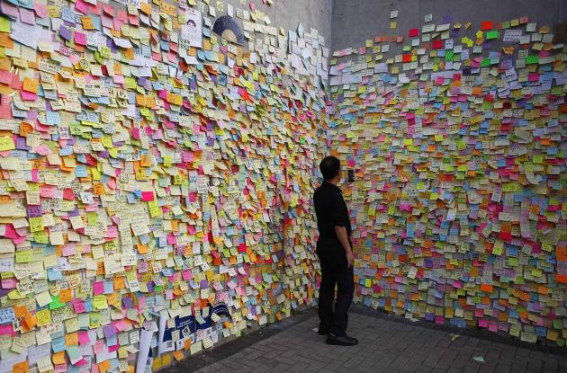 A man takes a picture on a wall full of messages left by pro-democracy protesters in Hong Kong.