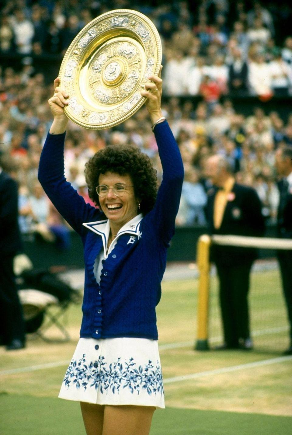 <p>Billie Jean King holds the trophy aloft after winning the Women's Singles event in 1975.</p>