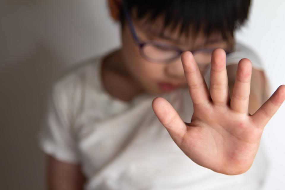Asian boy puts up hand to stop from being spanked
