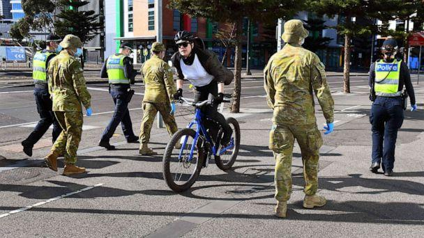 PHOTO: A cyclist passes a group of police and soldiers patrolling the Docklands area of Melbourne, Aug. 2, 2020, after the announcement of new restrictions to curb the spread of the COVID-19 coronavirus. (William West/AFP via Getty Images)