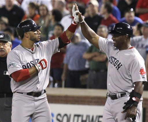 Boston Red Sox's Mike Aviles, left, gets congratulations from first base coach Alex Ochoa after Aviles' single drove in the go-ahead run during the ninth inning of a baseball game against the Texas Rangers on Tuesday, July 24, 2012, in Arlington, Texas. The Red Sox won 2-1. (AP Photo/LM Otero)