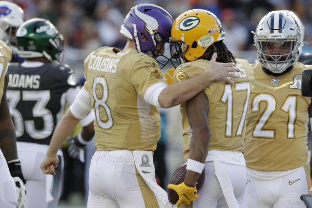 NFC quarterback Kirk Cousins, of the Minnesota Vikings, congratulates NFC wide receiver Davante Adams, of the Green Bay Packers, after Adams scored a touchdown, during the second half of the NFL Pro Bowl football game against the AFC, Sunday, Jan. 26, 2020, in Orlando, Fla. (AP Photo/Chris O?Meara)