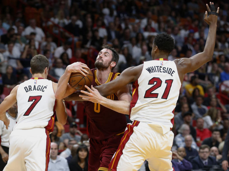 File- This April 10, 2017, file photo shows Cleveland Cavaliers forward Kevin Love (0) attempting a shot against Miami Heat center Hassan Whiteside (21) and guard Goran Dragic (7) during the first half of an NBA basketball game, in Miami. The Cavaliers have fallen back on excuses — some legitimate — to explain this disjointed season. Well, those don't matter now. James and the defending champs enter the playoffs staring at a possibly dangerous path. (AP Photo/Wilfredo Lee, File)