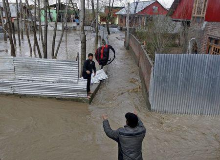 A man throws his belongings towards another to be moved to a safer place at a flooded neighbourhood after incessant rains in Srinagar March 30, 2015. REUTERS/Danish Ismail
