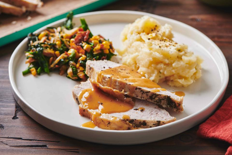 This May 2019 photo shows a plate of turkey, mash potatoes and gravy and a side of sauteed broccoli rabe, corn and onions with crispy bacon, on a table in New York. If you remember that the turkey breast will take less time to cook than the legs, and that you can get a head start on your gravy, Thanksgiving will be a whole lot less stressful. (Cheyenne Cohen/Katie Workman via AP)