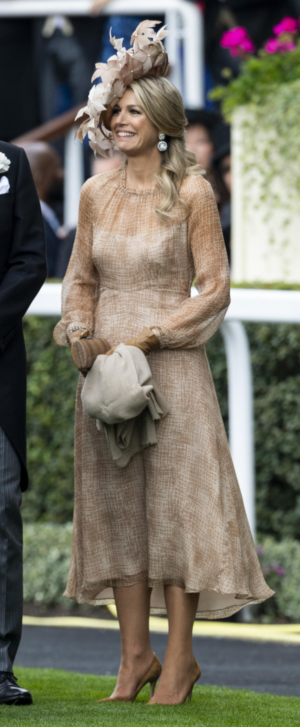Queen Maxima of The Netherlands wore a nude-blush midi dress with semi-sheer cuffed sleeves and a floral hat, with earrings from the Stuart Tiara. <em>[Photo: Getty]</em>
