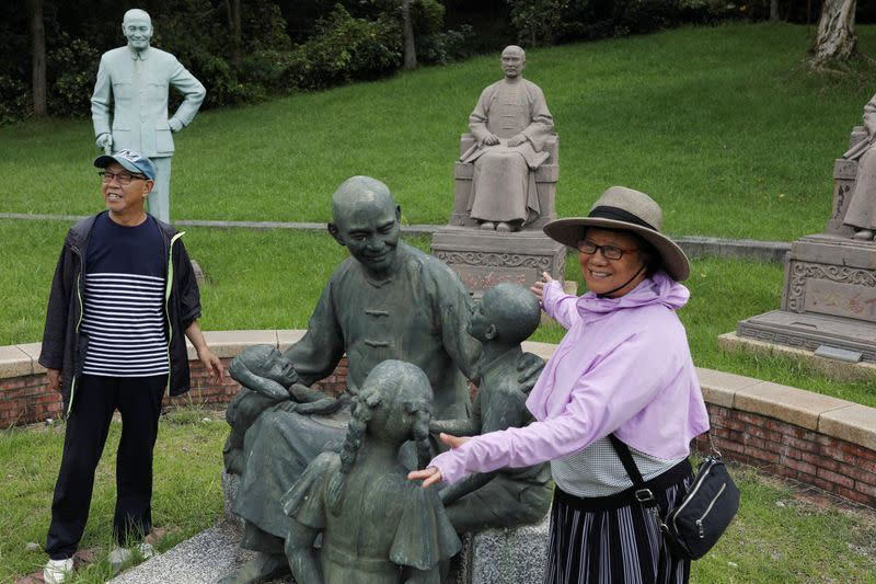 Visitors take photos of a statue of Chiang Kai-shek in Taoyuan