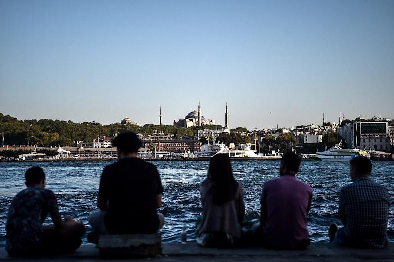 People sit on the docks of the Karakoy district, across from the Hagia Sophia former mosque, enjoying the attractions of Istanbul