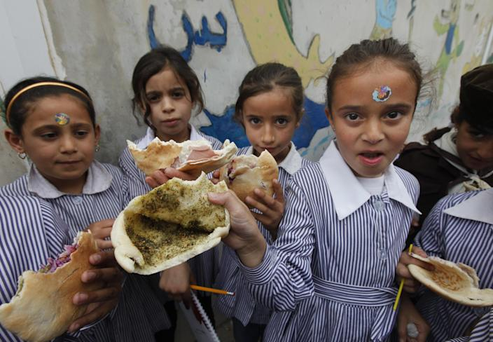 Palestinian students hold up their sandwiches of pita bread stuffed with olive oil and zaatar, a mixture of herbs and spices, brought from home, during their half-hour mid-day break at about 11 a.m. in the West Bank city of Nablus, Tuesday, May 6, 2014. Palestinian children in the West Bank usually eat during recess in the schoolyard, as there are no dining rooms in schools. (AP Photo/Majdi Mohammed)