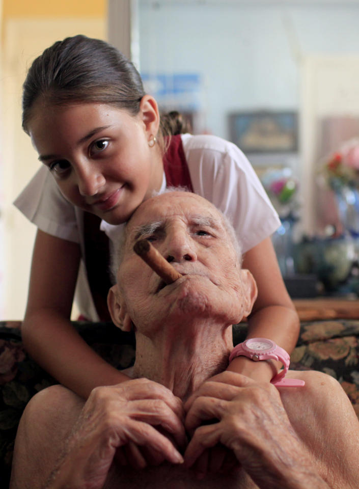 In this April 23, 2013 photo, Conrado Marrero, the world's oldest living former major league baseball player, poses for a picture with his great-granddaughter Sandra Marrero, 12, two days before is 102nd birthday at his home as he holds an unlit cigar in his mouth in Havana, Cuba. In addition to his longevity, the former Washington Senator has much to celebrate this year. After a long wait, he finally received a $20,000 payout from Major League baseball granted to old-timers who played between 1947 and 1979. The money had been held up since 2011 due to issues surrounding the 51-year-old U.S. embargo on Cuba, which prohibits most bank transfers to the Communist-run island. But the payout finally arrived in two parts, one at the end of last year, and the second a few months ago, according to Marrero's family. (AP Photo/Franklin Reyes)
