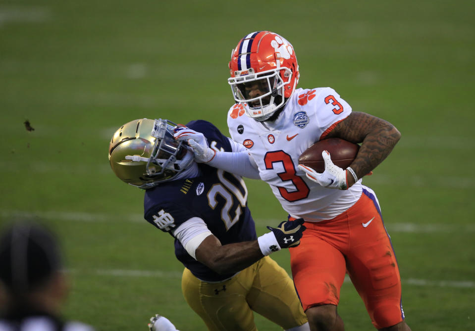 Clemson wide receiver Amari Rodgers (3) fends off Notre Dame safety Shaun Crawford (20) as he runs for a first down during the first half of the Atlantic Coast Conference championship NCAA college football game, Saturday, Dec. 19, 2020, in Charlotte, N.C. (AP Photo/Brian Blanco)
