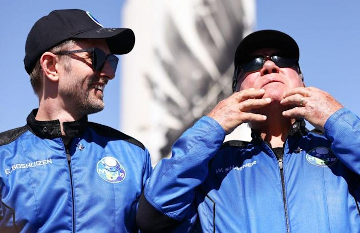 """""""Star Trek"""" actor William Shatner gestures as Planet Labs co-founder Chris Boshuizen looks on after their Blue Origin flight to space on October 13, 2021."""