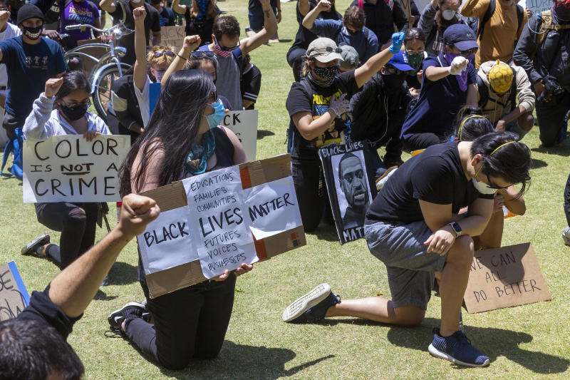 Demonstrators kneel down for 8 minutes and 46 seconds Thursday, June 4, 2020, in downtown Los Angeles during a protest over the death of George Floyd, who died May 25 after being restrained by police in Minneapolis. (AP Photo/Damian Dovarganes)