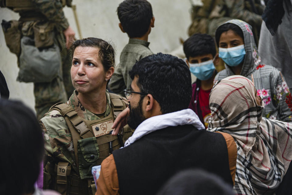 In this image provided by the U.S. Marines, a U.S. Airman with the Joint Task Force-Crisis Response speaks with families who await processing during an evacuation at Hamid Karzai International Airport in Kabul, Afghanistan, Friday, Aug. 20, 2021. (Cpl. Davis Harris/U.S. Marine Corps via AP)