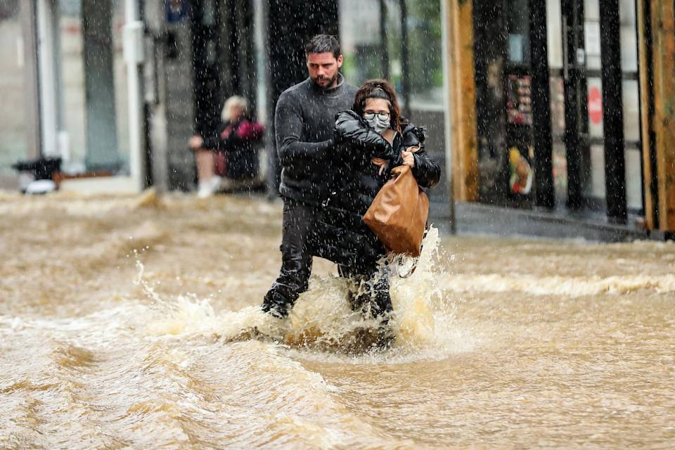 A man helps a woman navigate a flooded street in the city center of Spa, Belgium, on Thursday