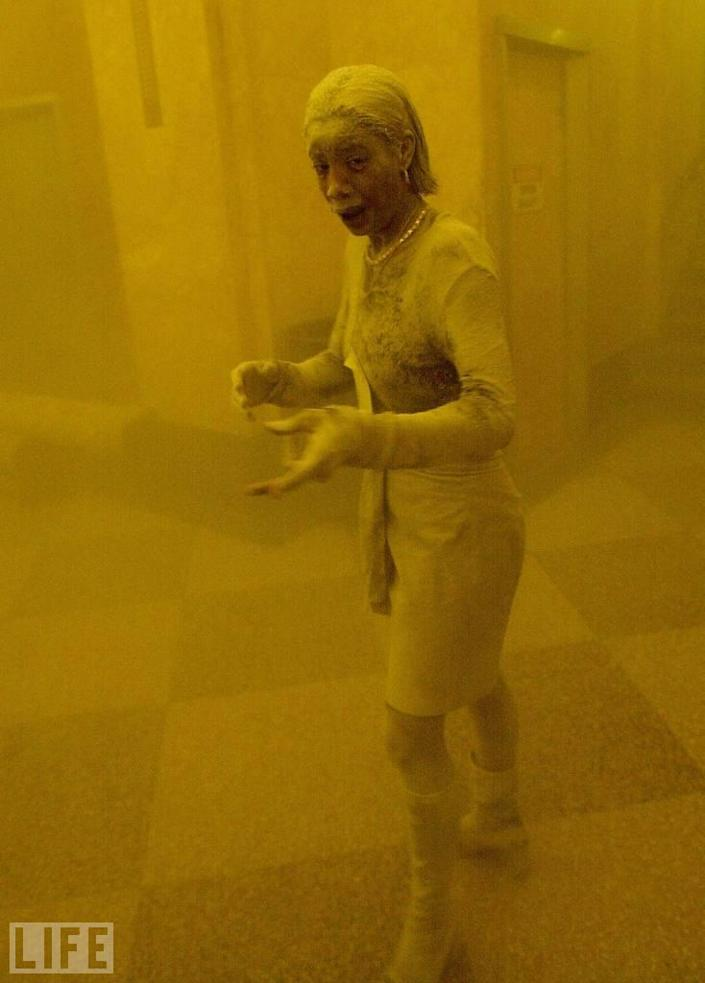 "Stunned, frightened Marcy Borders, 28, is covered in dust as she takes refuge in an office building after one of the World Trade Center towers collapsed. Borders was caught outside on the street as the cloud of smoke and dust enveloped the area, and raced into the building seeking shelter -- a building into which freelance photographer Stan Honda had also fled. ""She was sort of this ghostly figure,"" Honda told LIFE.com, ""covered in grey-white dust, and I thought that this was an amazing thing to see, that this would make an important picture of what was happening out there."" Of all the images from 9/11, Honda's picture is perhaps the most immediate representation of the collective and individual shock felt by those who were actually there, in lower Manhattan, when the towers fell. (Photo: STAN HONDA/AFP/Getty Images)<br><br>For the full photo collection, go to <a href=""http://www.life.com/gallery/63651/confronting-terror-faces-of-911#index/0"" rel=""nofollow noopener"" target=""_blank"" data-ylk=""slk:LIFE.com"" class=""link rapid-noclick-resp"">LIFE.com</a>"