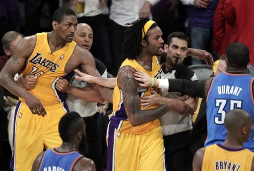 Los Angeles Lakers' Metta World Peace, left, and teammate Jordan Hill are restrained by referees in a scuffle with the Oklahoma City Thunder during the first half in Game 3 of an NBA basketball playoffs Western Conference semifinal game in Los Angeles, Friday, May 18, 2012. (AP Photo/Jae C. Hong)