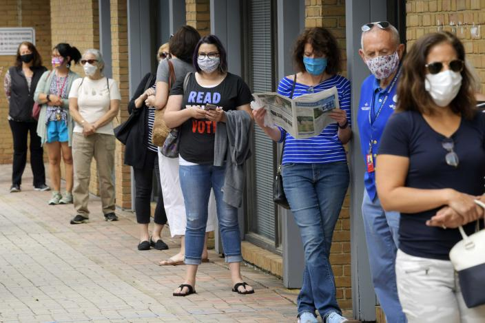 """FILE - In this Sept. 18, 2020 file photo, Alexandria residents wait in a socially distance line to cast their ballots for the November presidential election on first day of early voting in Virginia, at the Voter Registration Office in Alexandria, Va. A severed fiber optic cable shut down Virginia's online voter registration system Tuesday, Oct. 13 the last day to register before the November general election. The Virginia Department of Elections said in statement on Twitter that a """"fiber cut"""" was affecting connectivity for multiple agencies, including the citizen portal and registrar's offices, and technicians were working to repair the problem. (John McDonnell/The Washington Post via AP, File)"""