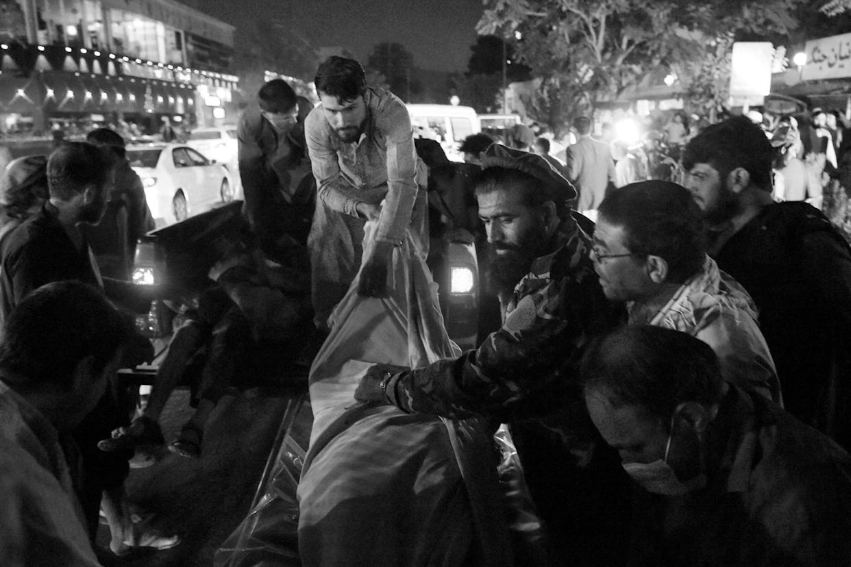 Volunteers and medical staff unload bodies from a pickup truck outside a hospital after two powerful explosions killed at least six people outside the airport in Kabul on Thursday.